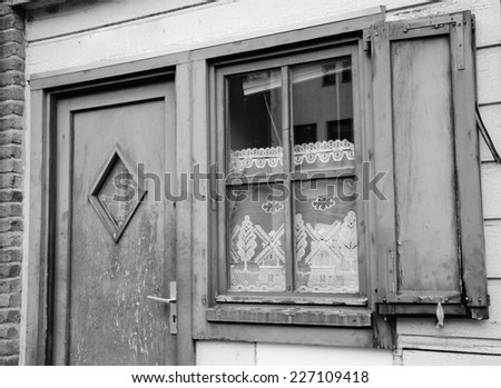A front of house. A door and a window with lace curtain decorated with windmill and tree pattern and wooden hinged shutters. (Amiens, Picardy, France)  Rustic background. Aged photo. Black and white. - stock photo