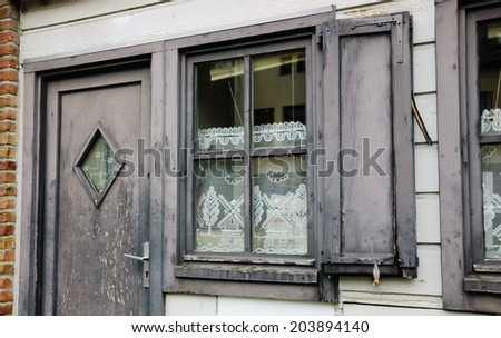 A front of the house. A door and a window with white lace curtain decorated with windmill and tree pattern and wooden hinged shutters . (Amiens, Picardy, France)  Rustic background. - stock photo