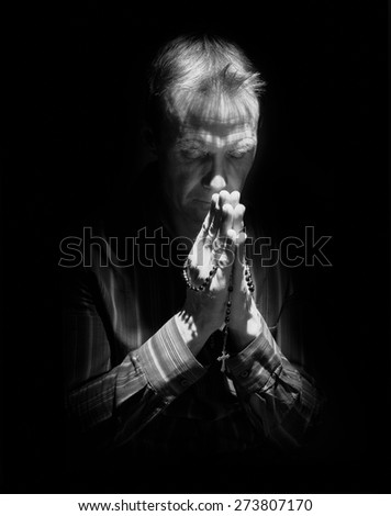 A front view of a man praying in the dark with the light shining on the side of him. Instagram styling applied. Small amount of added grain. - stock photo