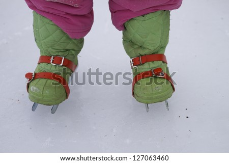 A front view of a small child wearing trainer skates on a frozen pond in northern Maine