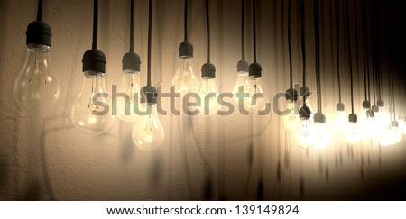 A front view row of displayed illuminated hanging light bulbs casting various shadows on a brown wall background - stock photo