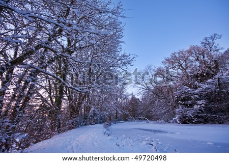 A frozen lake with a snowy footpath running alongside in winter. Photo taken at sunset twilight, with blue sky in the background. - stock photo