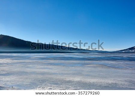A frozen lake with mist in the horizon. - stock photo