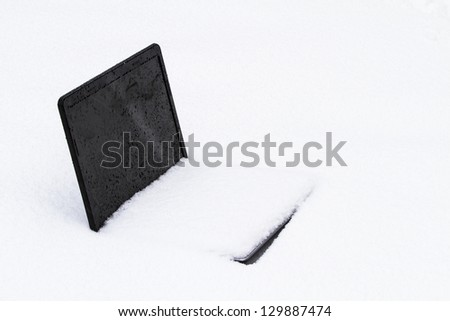 A frozen laptop computer half buried in  snow drift - stock photo