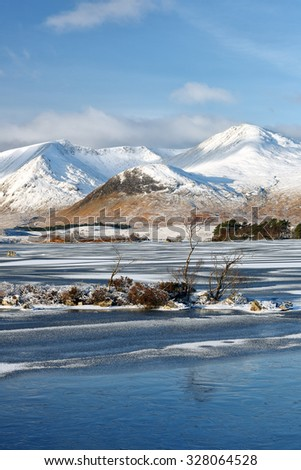 A frozen Loch and snow capped covered mountains in the Scottish highlands.  - stock photo
