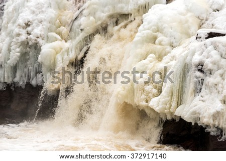 A frozen waterfall. The ice is dirty with traces of mud in it. There are large ice formations and icicles. Water is still flowing between the ice. The falls are in Saint George, New Brunswick, Canada. - stock photo