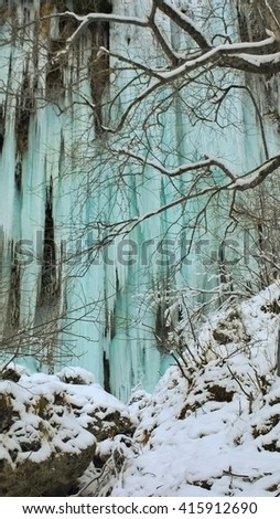 a frozen waterfall with blue water - stock photo