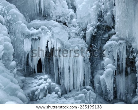 A frozen waterfall with ice in a blue and white color in winter. Winter background. - stock photo