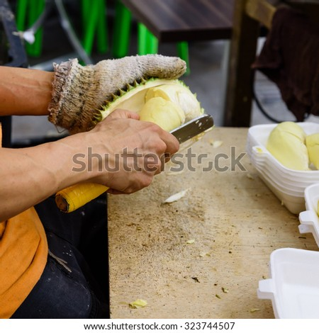 A fruits shop owner is using knife to peel durian in the wet market in Singapore. After peeling durian are packaged into fresh to-go, ready to eat, convenience packs and sell locally