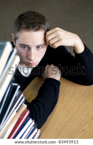 A frustrated and stressed out college student looks up at the high pile of textbooks he has to go through to do his homework assignment. - stock photo