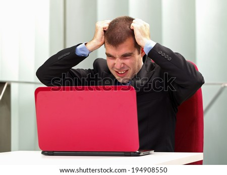 A frustrated businessman sitting in his office, in front of his laptop - stock photo