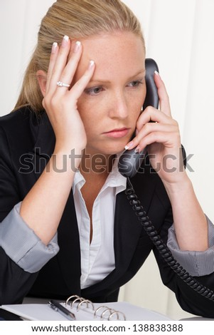 a frustrated woman phoned the office. stress and strain in the workplace. - stock photo