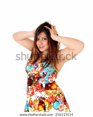A frustrated young woman standing for white background with her hands on her head, messing with her hair, isolated for white background.  - stock photo