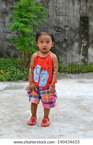 A full body portrait of beautiful Asian little girl taking a step