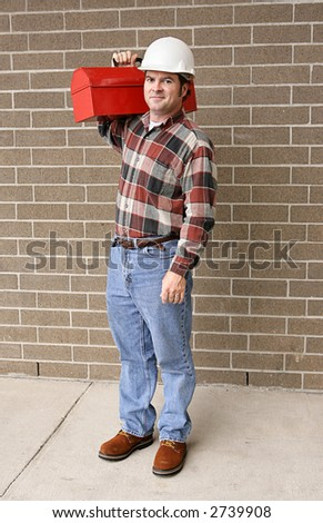 A full body view of a handsome blue collar worker with his toolbox and hardhat. - stock photo
