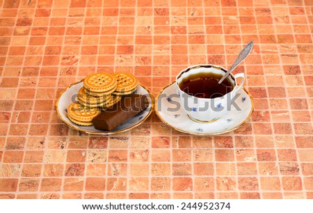 A full cup of tea, spoon, saucer, biscuits and cookies are on multicolor table - stock photo