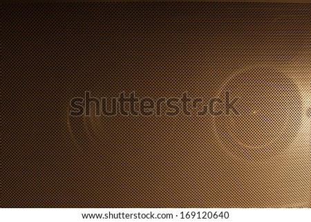 A full frame shot of the mesh of a speaker grille.  The speaker is lit from the side with a golden light source providing a pleasant gradient. - stock photo