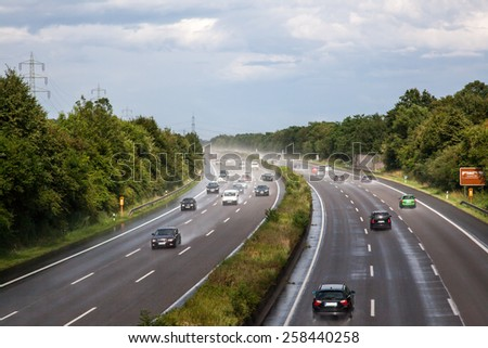 A full german highway with wet roads and poor visibility. - stock photo
