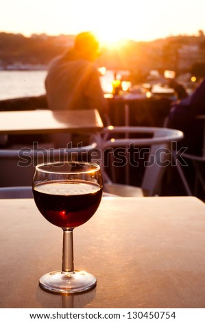 A full glass of red Porto wine on a table in a bar in Portugal at sunset. - stock photo