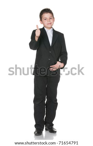 A full height portrait of a cheerful boy in black suit holding his thumb up; isolated on the white background - stock photo