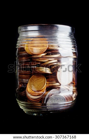 A full jar of Brazilian coins isolated on black background - stock photo