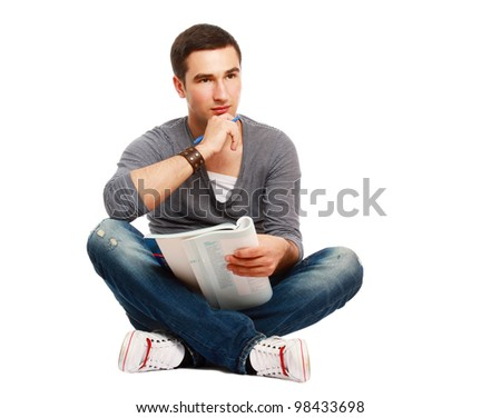 A full-lenght portrait of a young handsome college guy sitting on the floor and studying, isolated on white - stock photo