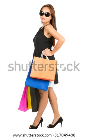 A full length portrait of confident Asian female shopper stands profile posing with arms akimbo wearing a stylish black dress with colorful department store bags sunglasses looking at camera. Isolated - stock photo