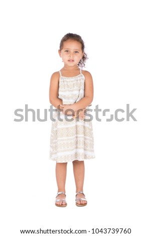A full-length shot of a little girl wearing a beautiful dress standing, holding hands together, isolated on white background.