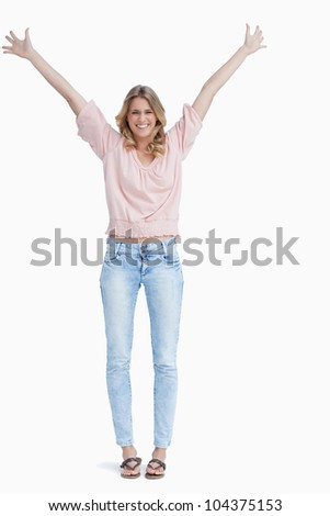 A full length shot of a smiling woman who has her arms raised up against a white background