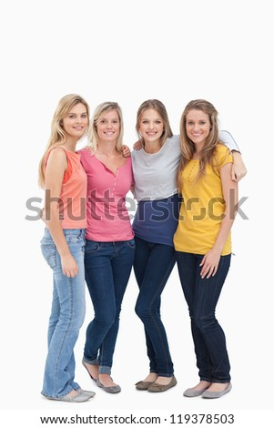 A full length shot of four friends standing beside each other and smiling