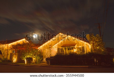 A full moon peaks over a home with Christmas lights in Laguna Beach, California. There has not been a full moon at Christmas since 1977. The next one wonâ??t be until 2034 - stock photo