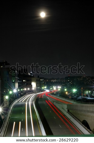 A full moon rises over a highway running through Washington DC. - stock photo