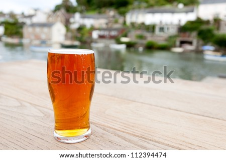A full pint of English real ale on a wooden table outside a riverside pub.  Differential focus on the glass. - stock photo