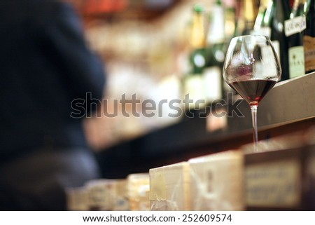 A full wineglass on a shelf in a wine store - stock photo