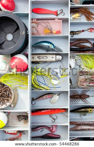A fully stocked fisherman's tackle box fully stocked with lures and gear for fishing. - stock photo