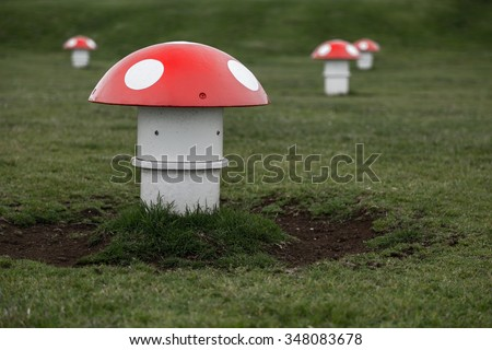 A fun, colorful set of mushrooms for children to balance on in a local park. Not your average balance beam. Fun and whimsical, the sky is the limit for the uses of this photo. - stock photo