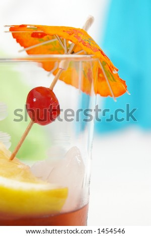 A fun garnish in a tropical punch drink. Focus is on cherry. - stock photo
