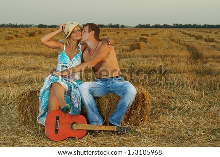 A  fun  pair of lovers on hay with guitar in summer at sunset. - stock photo
