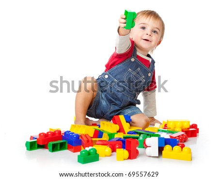 a funny boy is playing with lego. isolated on a white background - stock photo