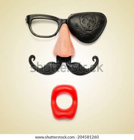 a funny face formed with fake mouth, nose and glasses with mustache and pirate patch on a beige background, with a retro effect - stock photo