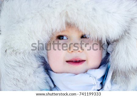 A funny happy child dressed in warm fur clothes  laughs and smiles. Close-up portrait. The concept of winter, frost and snow, cold weather, Cool temperature and Christmas