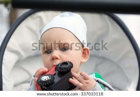 A funny little baby boy with toy in a in a baby carriage