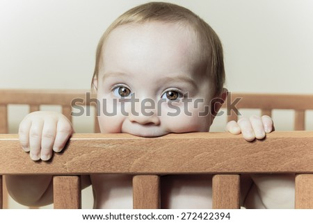 A Funny little baby with beautiful standing in a round white crib - stock photo