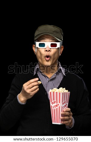 A funny take of a young Asian man being intrigued by a movie - stock photo