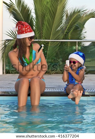 A funny woman with a child in Christmas hats, sitting poolside, take pictures on mobile phones