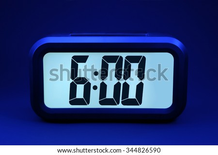 A futuristic digital clock on a black background at six o'clock in the morning.   - stock photo