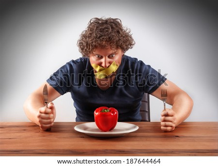 A gagged man wants to eat a red pepper. Holding a knife and a fork in his hand. Picture is made with dodge and burn effect. - stock photo