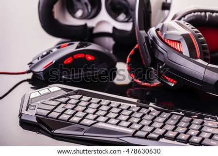 a gaming keyboard, mouse, headset and Virtual reality glasses shot over a dark reflective surface