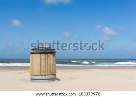 A garbage container on a clean beach - stock photo