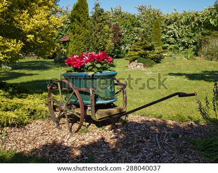 A garden decorated with an old wagon turned into a planter